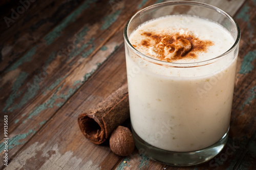 Garden Poster Milkshake Apple crumble smoothie milkshake topped with cinnamon and nutmeg spices. Served on a rustic wooden table.