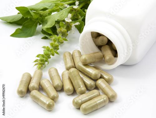Fotografia  Kapsułki z ziela wysypują się z butelki