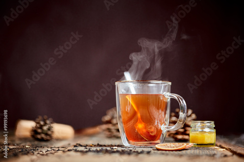 Steaming tea and honey on a wooden table
