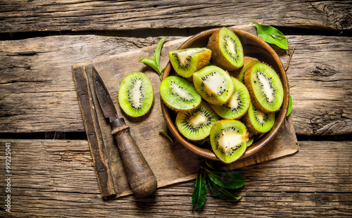 Fotografie, Tablou  sliced kiwi fruit in a wooden cup with a knife.