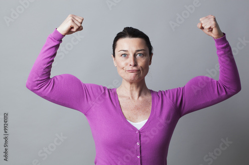 Photographie  muscle concept - happy 40s woman lifting her muscles up for metaphor of female freedom and power,studio shot