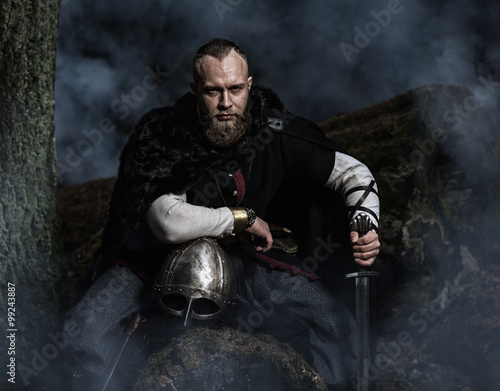 Viking with sword and  helmet on a background of smoky forest Poster