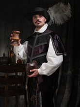 A Man In Period Costume And Hat Raises A Glass Of Wine