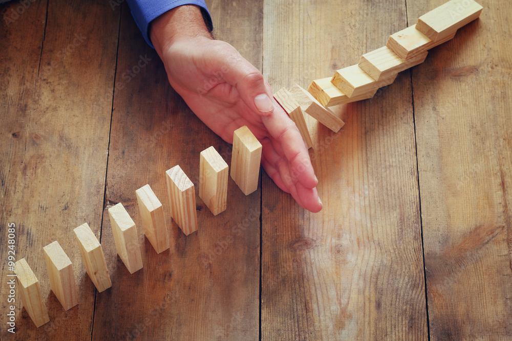 Fototapeta a male hand stoping the domino effect. retro style image executive and risk control concept