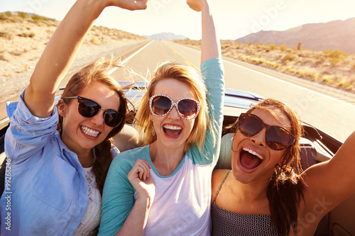 obraz lub plakat Three Female Friends On Road Trip In Back Of Convertible Car