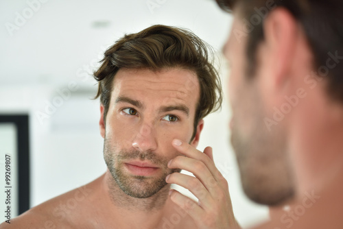 Fotografie, Obraz  Handsome man applying facial cream in front of mirror