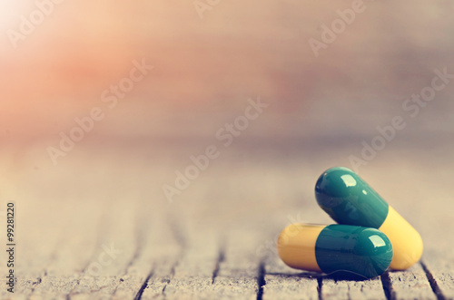 Poster Pharmacie Pharmacy background. Pills on a wooden table. Medicine. Natural background. Capsule. Close up. Sun