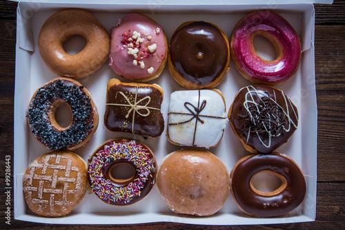 Poster Dessert Dozen artisan donuts in box on table
