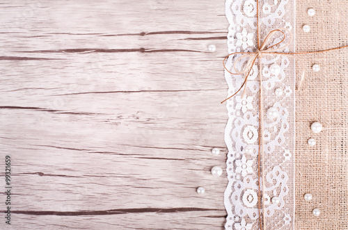 Valokuva  Lace, pearls, bowknot, canvas, sackcloth on wooden background