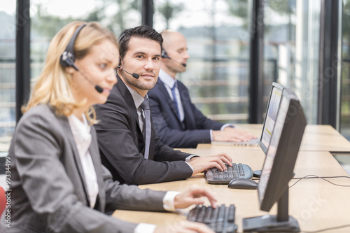 Young attractive man working in a call center Wallpaper Mural