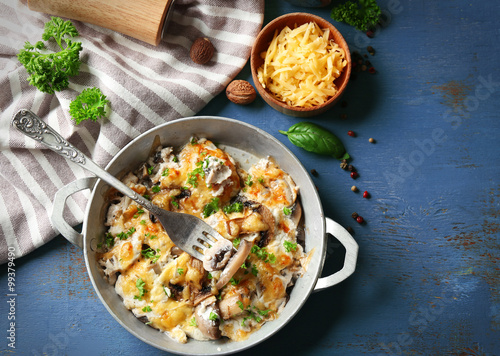 Roasted mushrooms, chicken and cheese gratin in pan, on color wooden background