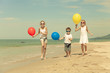Three happy children with balloons runing on the beach at the d