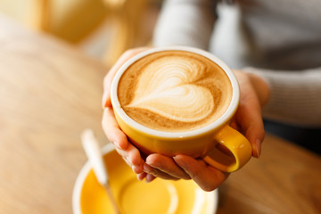 lady's hands holding cup with sth heart-shaped