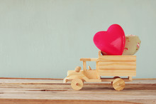 Photo Of Wooden Toy Truck With Hearts In Front Of Chalkboard. Valentine's Day Celebration Concept. Vintage Filtered
