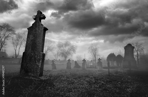 Fotografiet Old creepy graveyard on stormy winter day in black and white