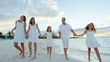 Caucasian family walking barefoot on beach together at sunset