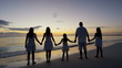 Caucasian family in sunset silhouette on the beach