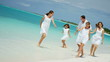 Caucasian family parents girls white clothes beach ocean island vacation tourism