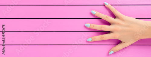 Deurstickers Manicure Female hand with blue nails over pink background