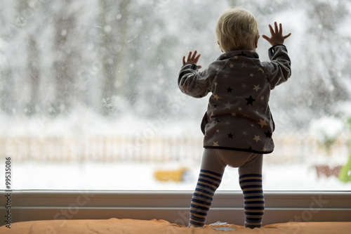 Toddler child standing in front of a big window leaning against Fototapet