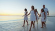 Barefoot Caucasian family wearing white clothes on the beach