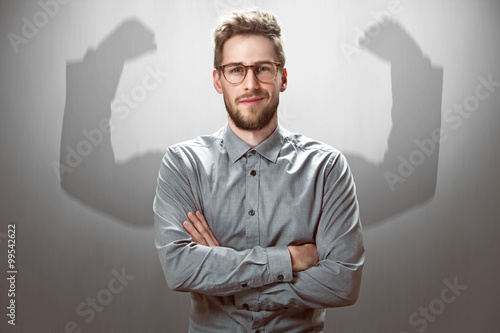 Slika na platnu Smiling Businessman with muscular shadow arms
