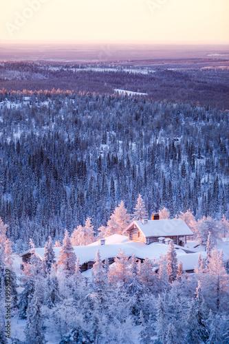 Papiers peints Scandinavie Winter scenery view over a cabin in frozen forest.