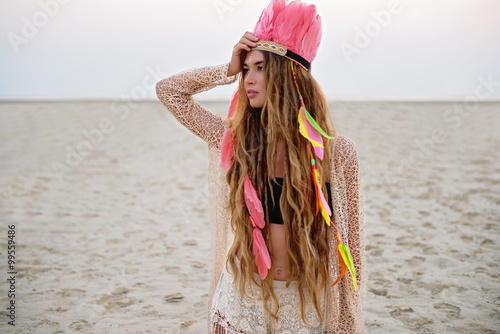 Fotografering  Boho chic beautiful model on the beach in peach colors
