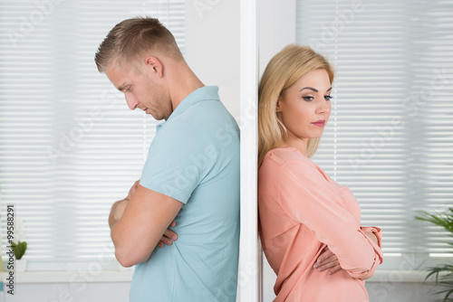 Photo Unhappy Couple Standing Back To Back At Home