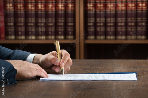 Lawyer Writing On Legal Documents At Desk Wallpaper Mural