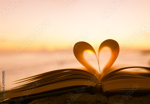 Photo Heart from a book page against a beautiful sunset.