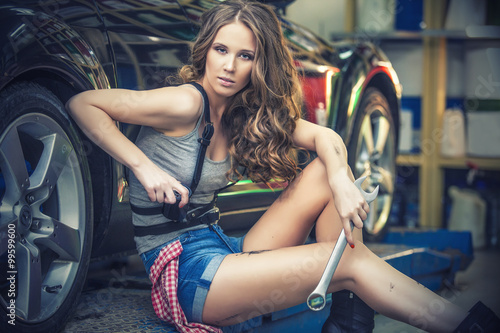 Zdjęcie XXL Beautiful sexy woman working to repair the car in the showroom