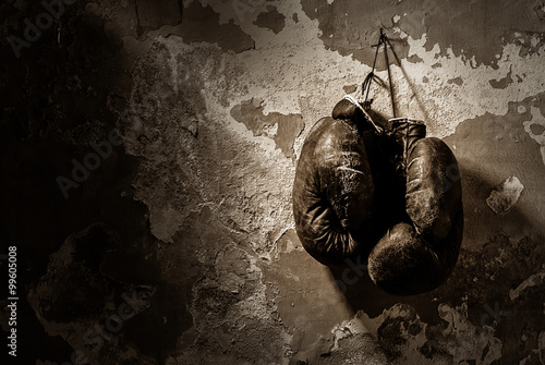 Canvas Print old boxing gloves hang on nail on texture wall