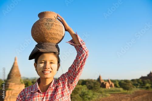 Fotografie, Obraz  Asian traditional female farmer carrying clay pot on head
