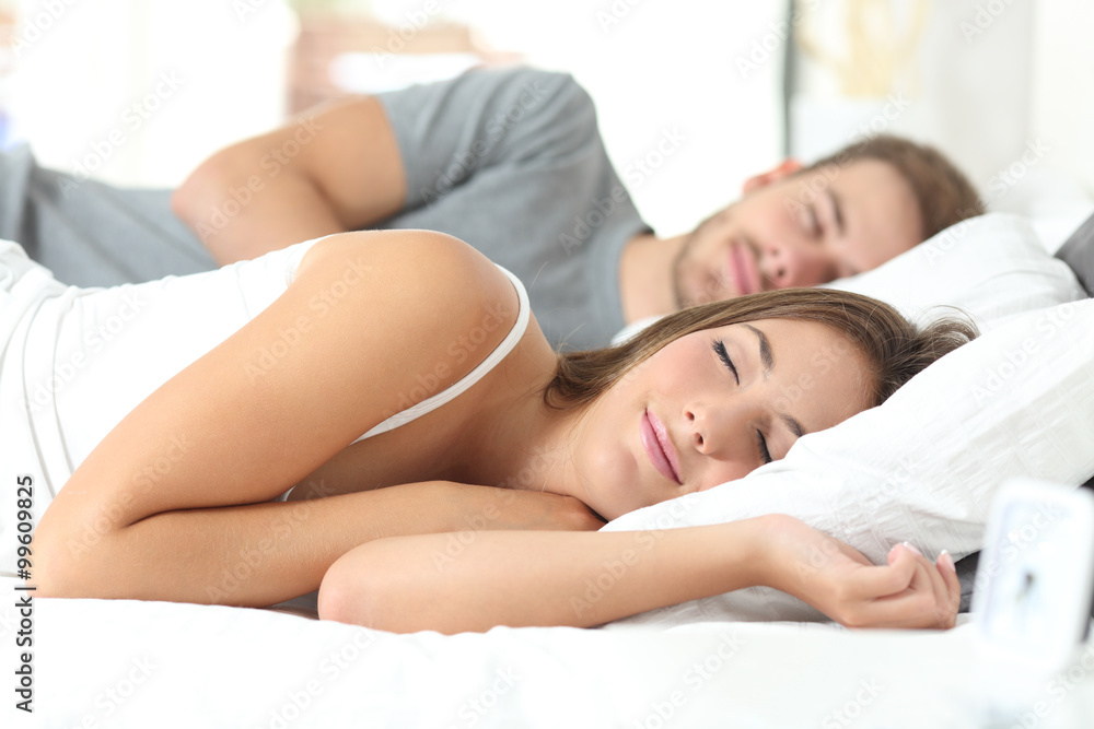 Fototapeta Couple sleeping in a comfortable bed