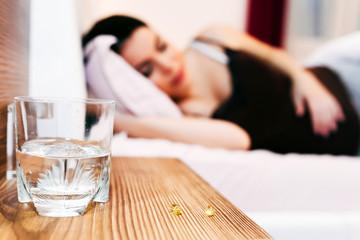 Obraz na płótnie Canvas Pregnant woman resting with pills at hand
