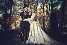 Dressed In Wedding Clothes Romantic Zombie Couple Walking On The Abandoned Cemetery.