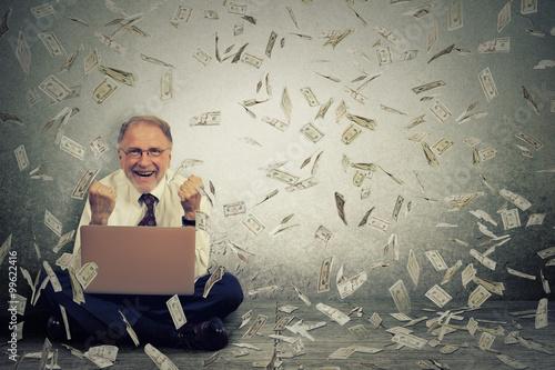 Fotografía  Hombre mayor que usa la computadora portátil construcción de negocio en línea que hace cuentas de banco del dólar que caen abajo