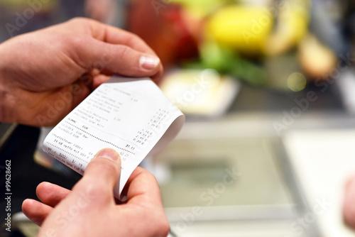 Fotografie, Obraz  Hände mit Kassenzettel an der Kasse im Supermarkt // hands with receipt at the c
