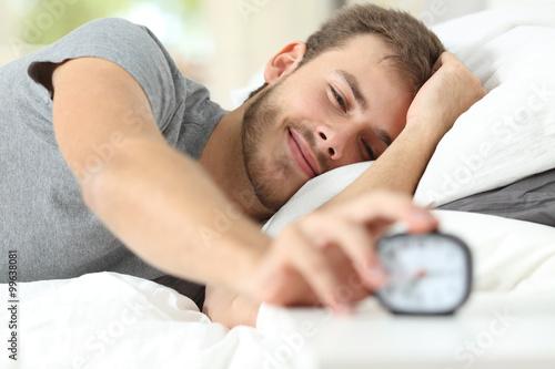 Obraz Happy wake up of a happy man stopping alarm clock - fototapety do salonu
