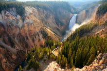 Lower Falls - Sunlight Illuminates The Spray As The Yellowstone River Crashes Over The Lower Falls In Yellowstone's Grand Canyon.