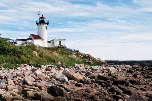 Fotografia, Obraz  Gloucester Harbor Lighthouse Over Rocky Shore in Low Tide