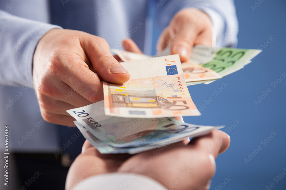 Fototapeta Businessman's  hands exchanging euro on blue background