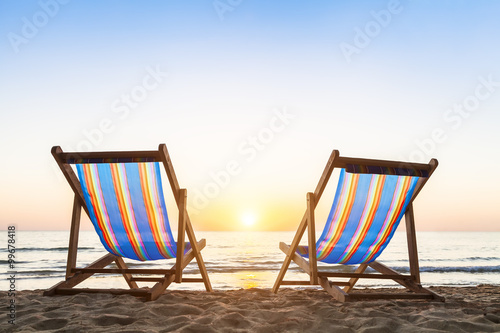 Two deck chairs on a sandy beach at sunset