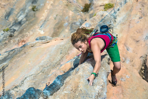 Fotografie, Obraz  Young Rock Climber ascending steep colorful rocky Wall Lead Climbing