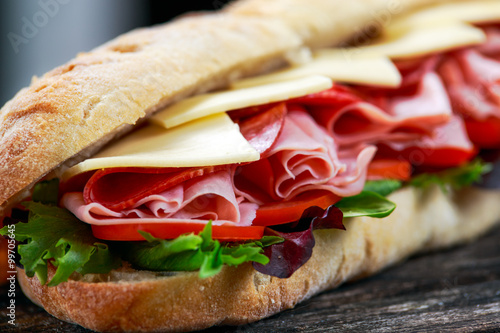 Photo Stands Snack Sandwich with lettuce, slices of fresh tomatoes, salami, hum and cheese.