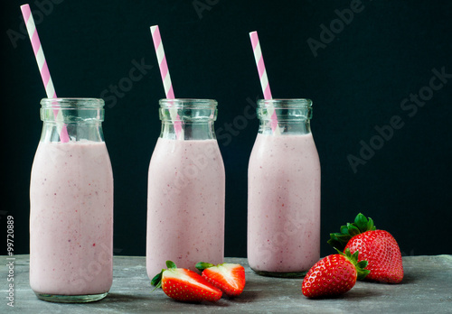 Foto op Aluminium Milkshake Smoothie milkshake made from fresh strawberry blended with kefir yogurt. Served in bottle style glasses and with fresh strawberries. Served on a stone slate table with colorful stripy straws.