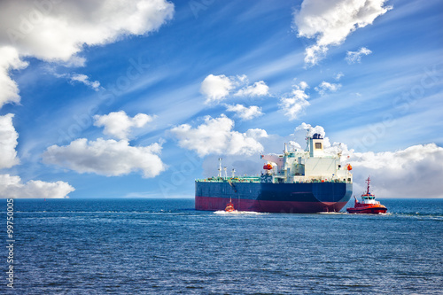 Fotografia  Tanker ship with escorting tugs leaving port.