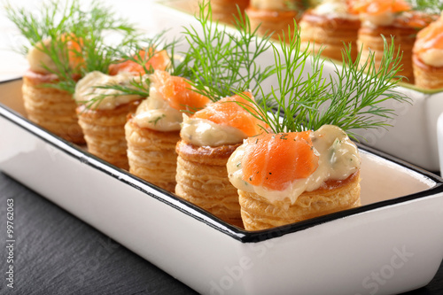 Photo sur Toile Entree Appetizer puff pastry with dill dip and salmon on stone tray