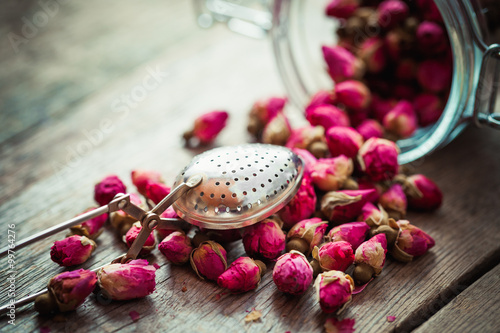 Fotografie, Obraz  Rose buds, tea strainer and glass jar on rustic wooden table. Re